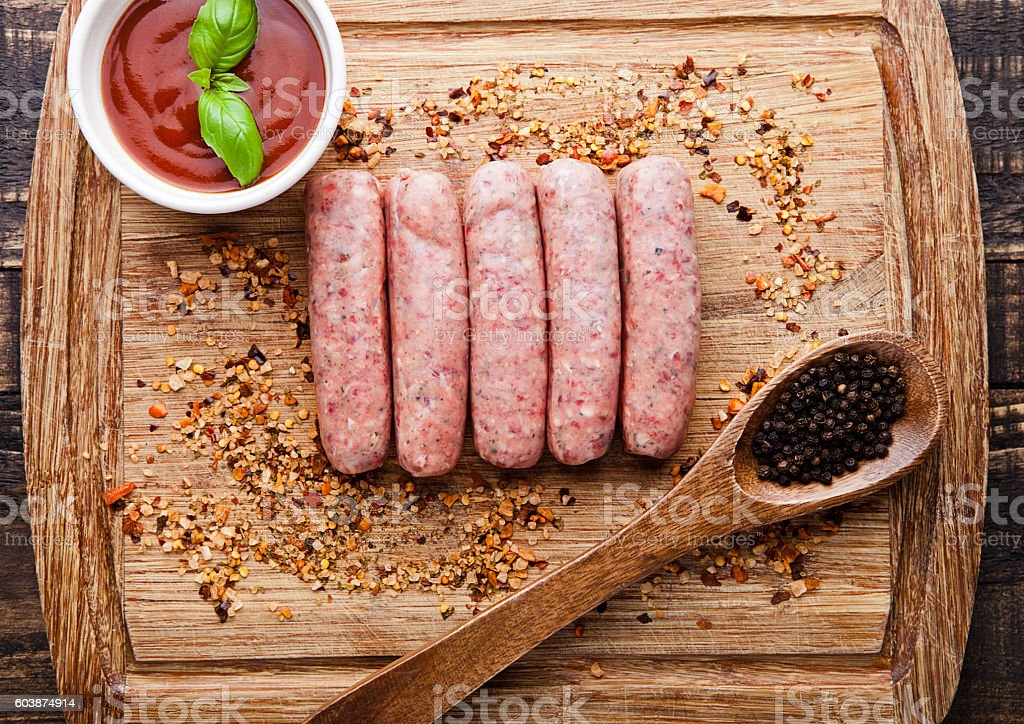 Raw beef sausages with pepper spoon and sauce stock photo