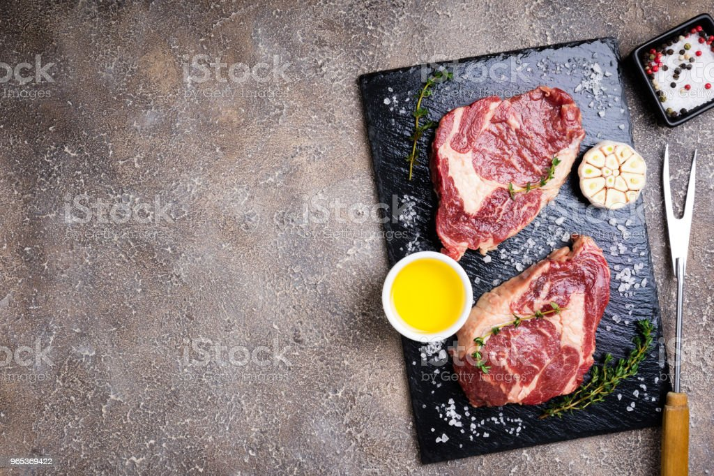 Raw beef steak and ingredients on cutting board. Raw meat on concrete background zbiór zdjęć royalty-free