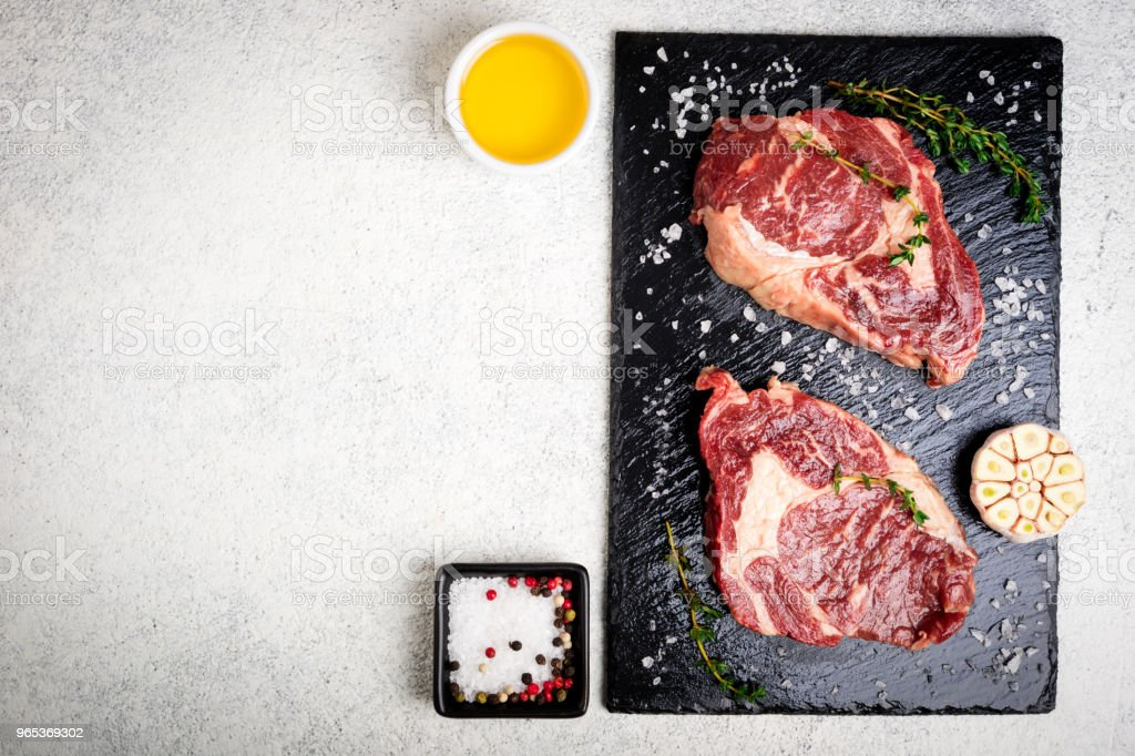 Raw beef steak and ingredients on cutting board. Raw meat on white concrete background. Top view zbiór zdjęć royalty-free