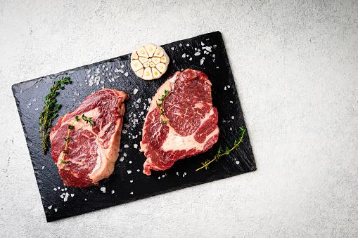 원시 쇠고기 스테이크 그리고 절단 보드에 재료입니다 흰색 콘크리트 바탕에 원시 고기입니다 상위 뷰 고기에 대한 스톡 사진 및 기타 이미지