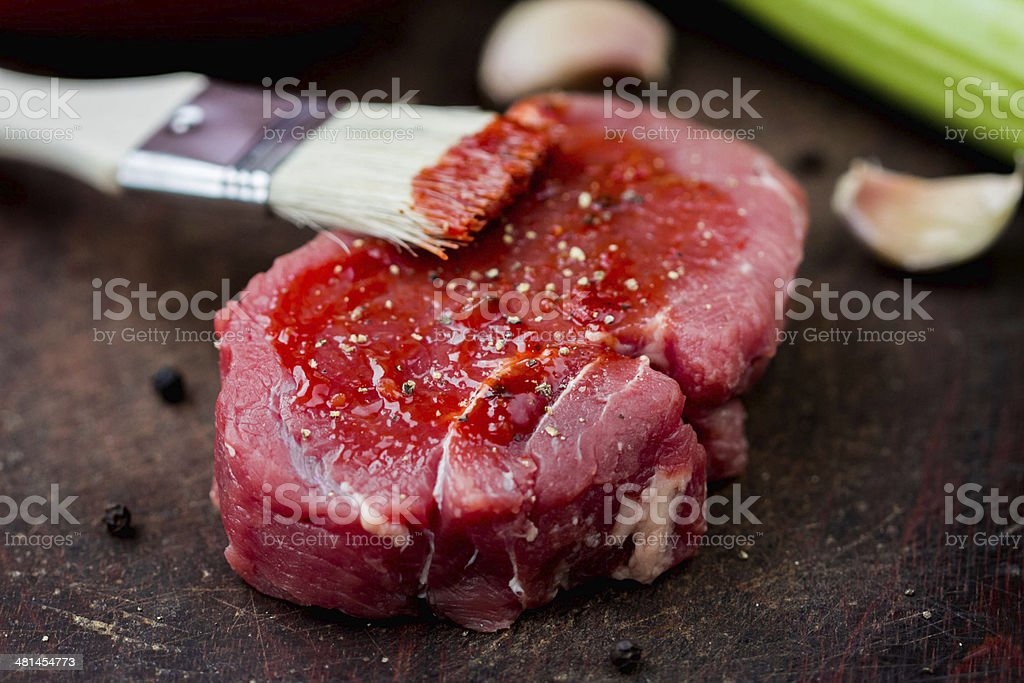 Raw beef steak, greased tomato sauce brush, cooking delicious stock photo