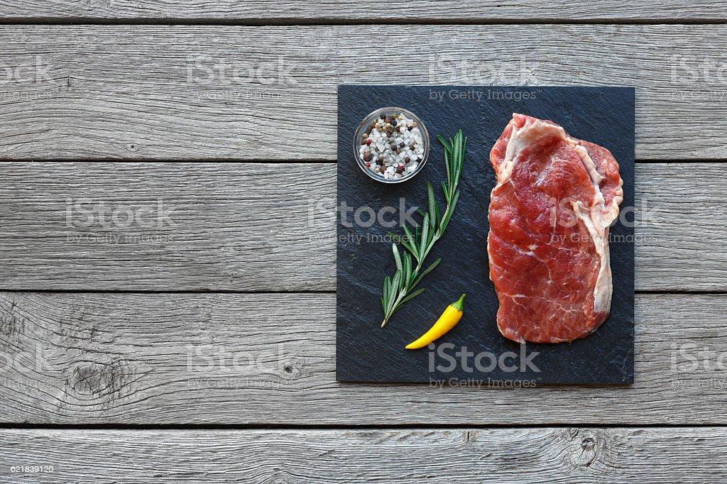 Raw beef steak on dark wooden table background, top view - foto de acervo
