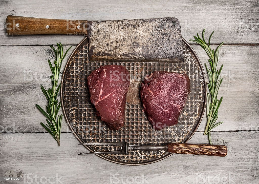 raw beef steak pan rosemary, meat cleaver fork rustic background stock photo