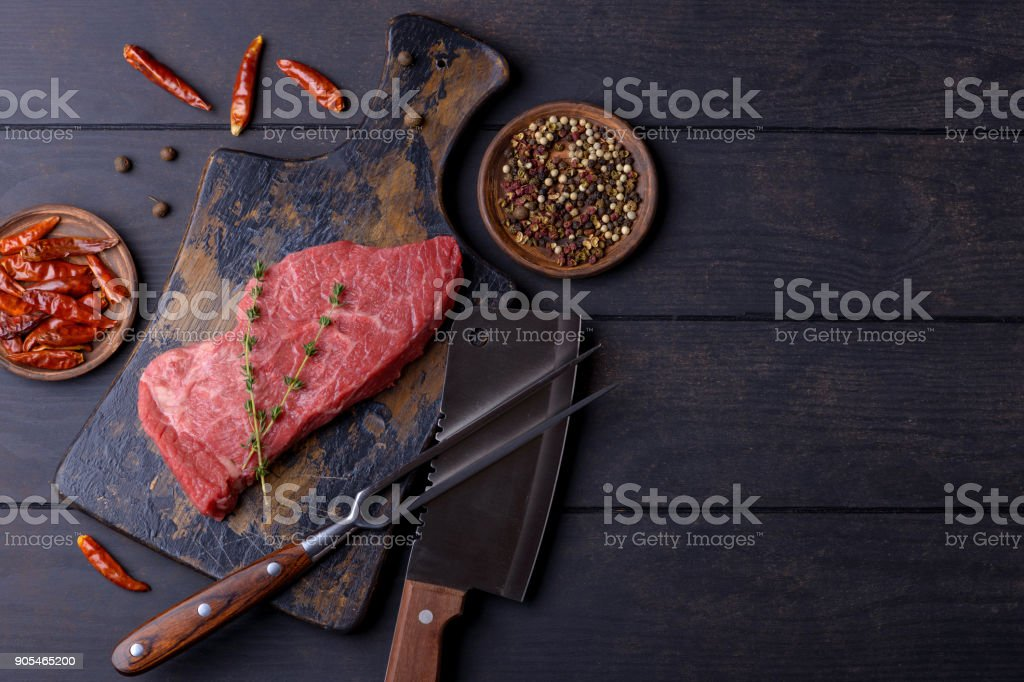 Raw beef steak with thyme and pepper stock photo