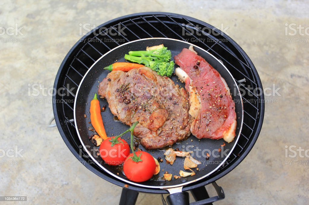 Raw beef steak with vegetables in frying pan on tiled floor background, food meat or barbecue stock photo