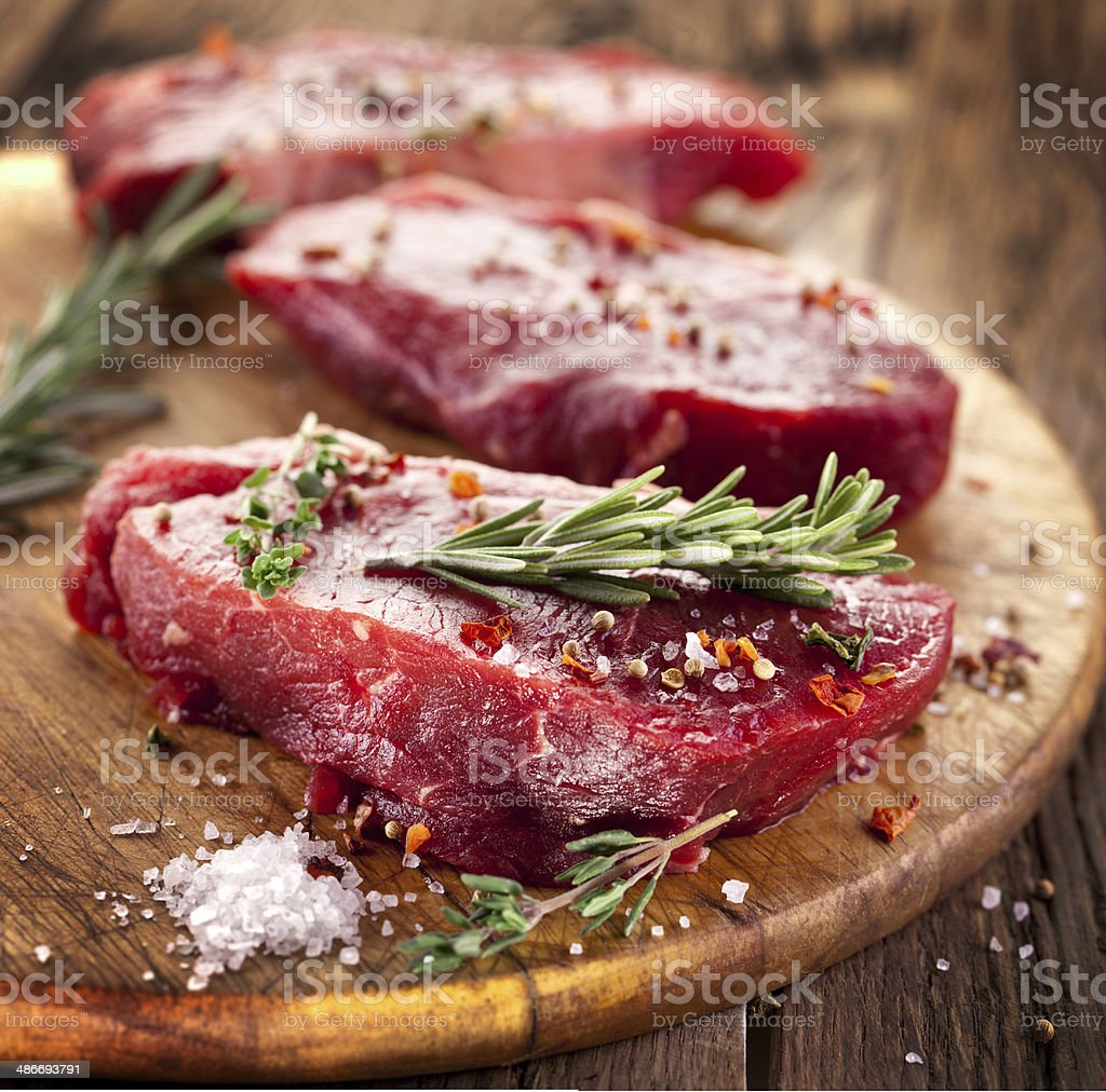 Raw beef steaks with rosemary. stock photo