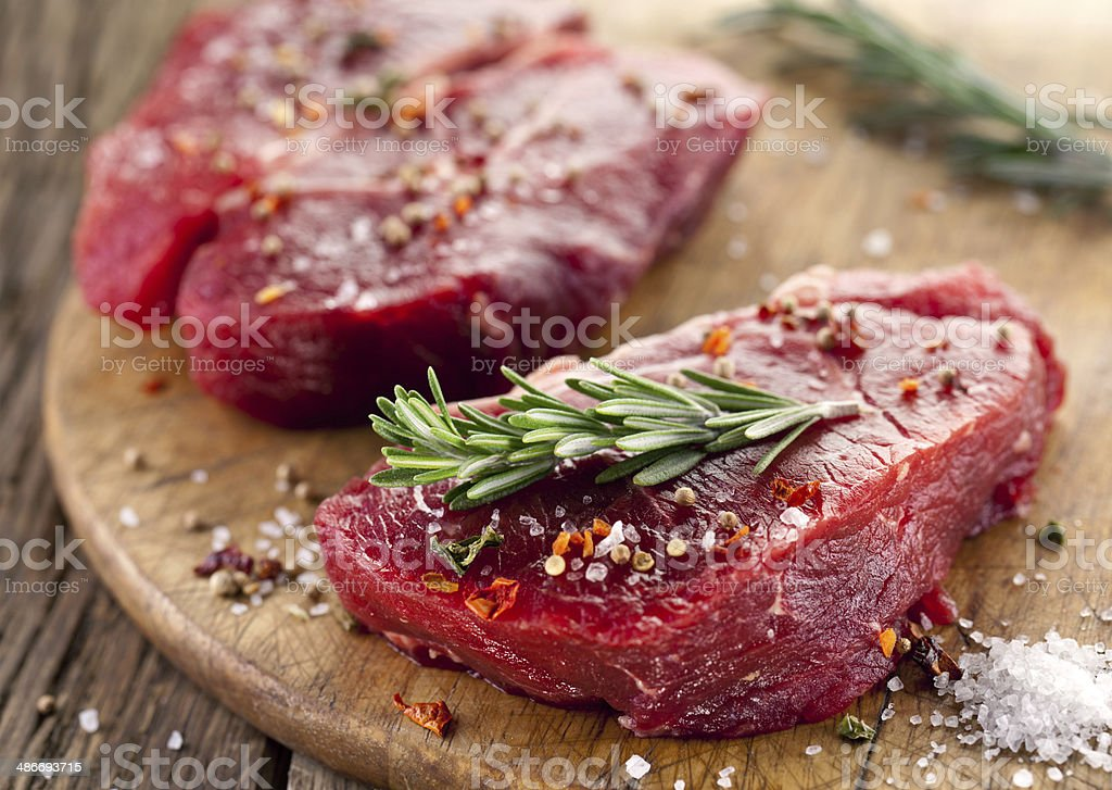 Raw beef steaks with spices. stock photo