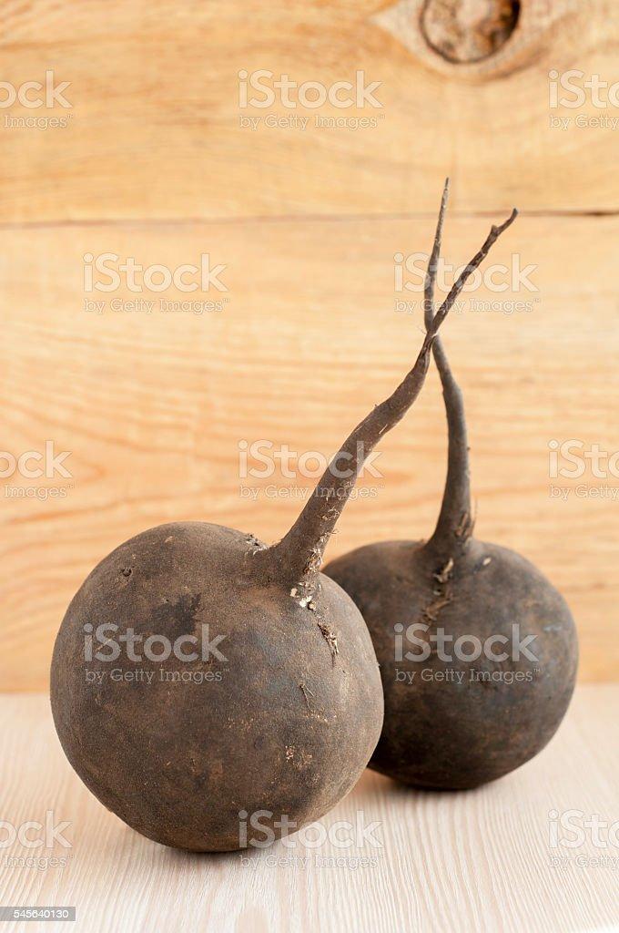 Raw black radish on wooden background stock photo