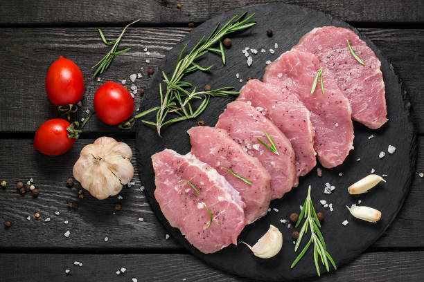 Raw boneless pork chops, vegetables, herbs and spices stock photo