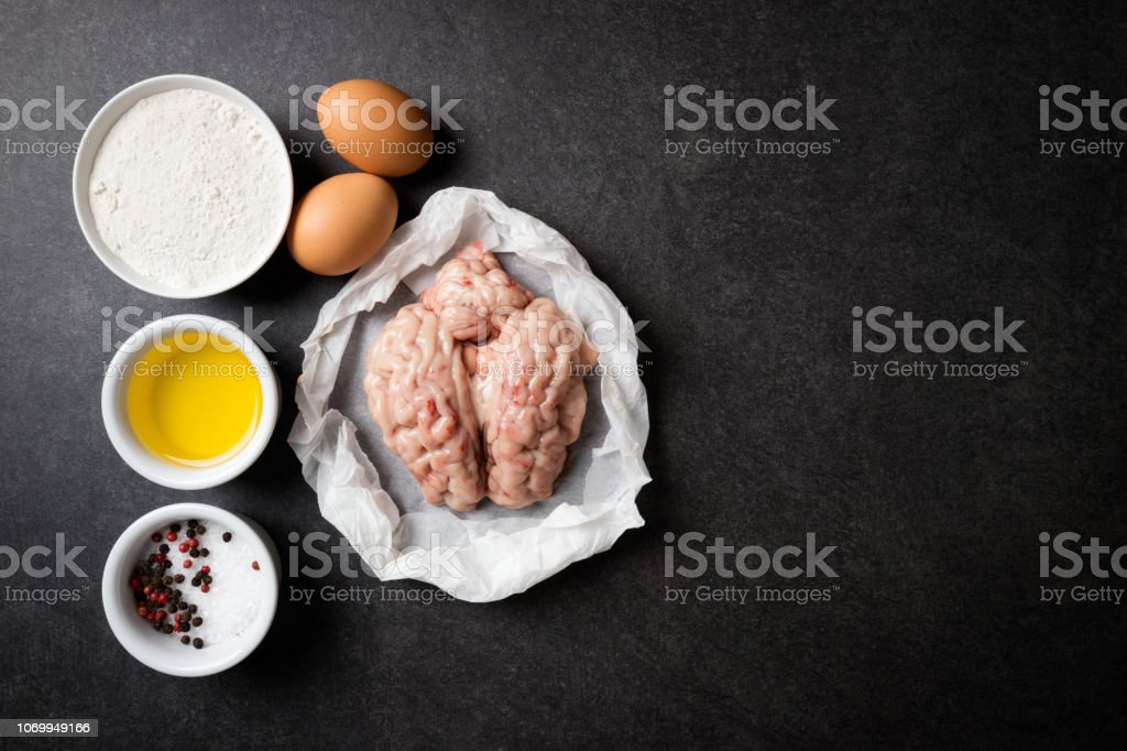 Raw brains and ingredients for cooking fried brains on a stone dark table. Calf or beef brains. Gourmet food. Top view stock photo