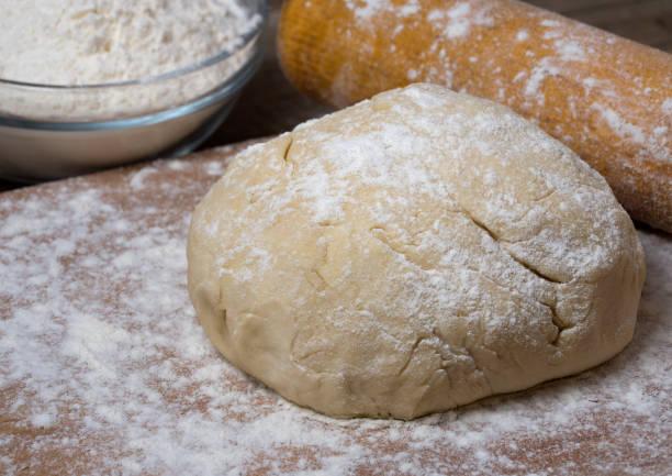 Rohes Brot oder Pizzateig auf rustikalem Holzhintergrund mit Mehlstaub. – Foto
