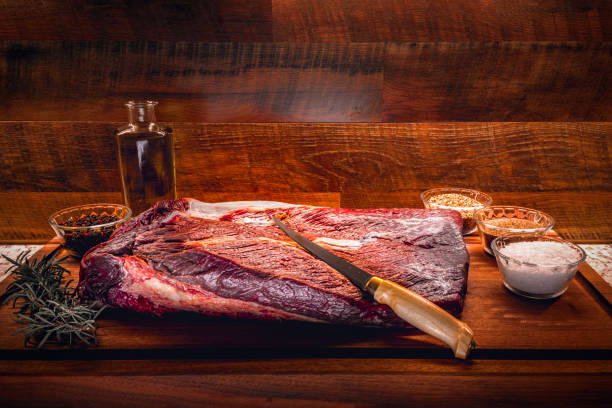 Raw brisket on a wooden cutting board with seasoning, salt and olive oil stock photo
