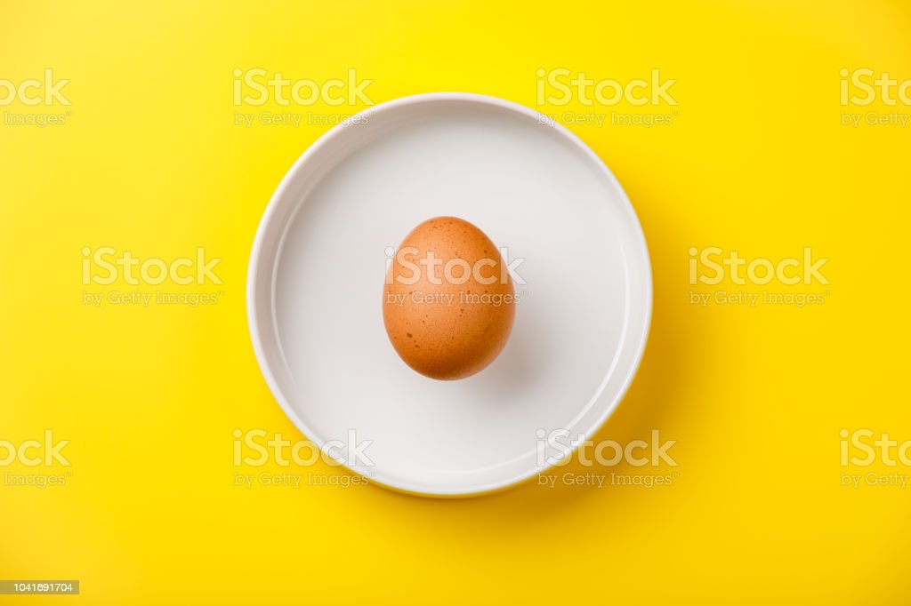 Raw brown chicken Egg on yellow background royalty-free stock photo