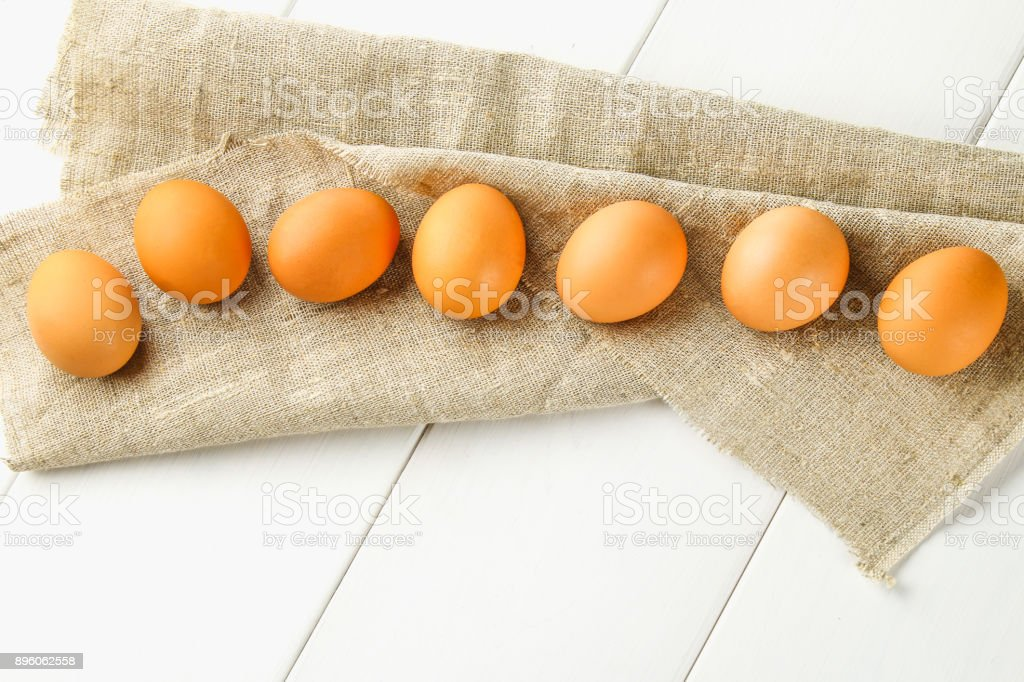 Raw Brown Chicken Eggs In One Row On Burlap On A White Wooden Table