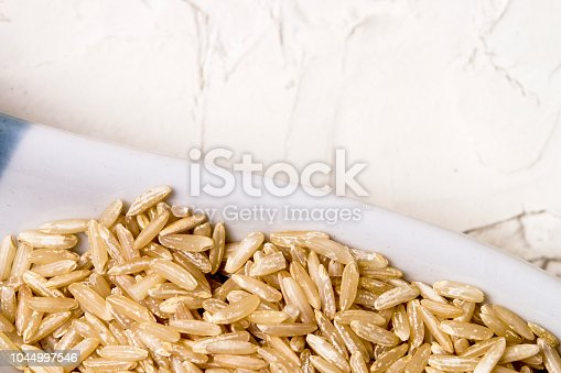 Raw brown rice on textured white background.  Healthy uncooked food. Vegan whole grain concept.