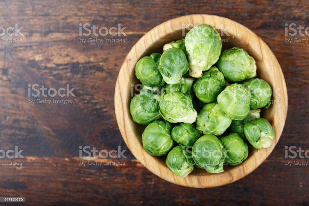 raw brussels sprouts in a plate on a wooden background stock photo