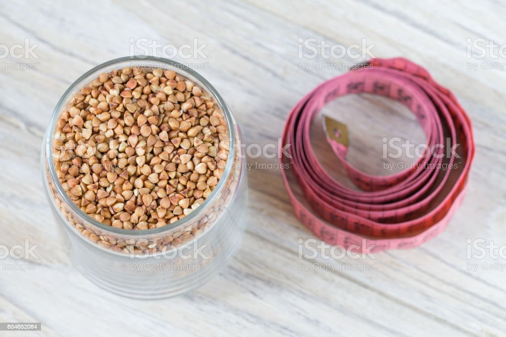 Raw buckwheat grain in glass bank and centimeter on a wooden background stock photo