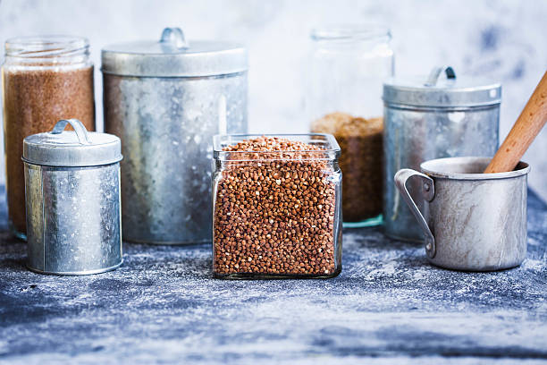 Raw Buckwheat In Glass Jar In a Composition Of Various Containers stock photo