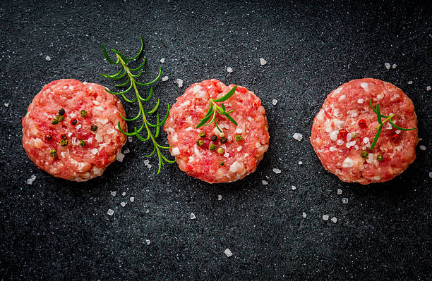 Raw burgers of beef and pork on a black board stock photo
