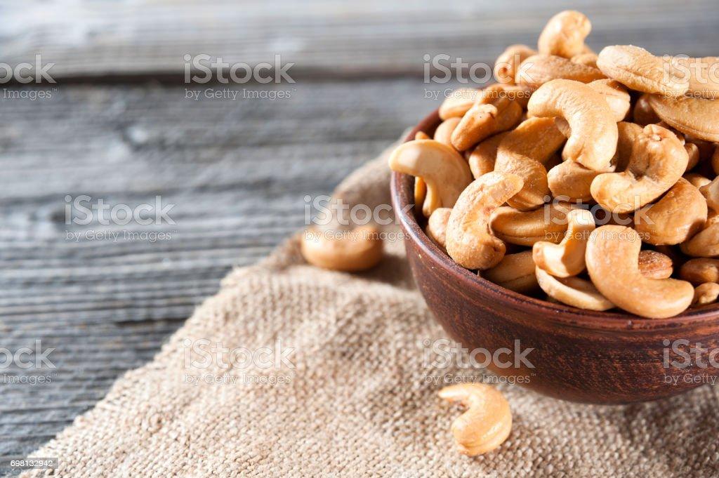 rohe Cashewnüsse in Keramikschale auf Holztisch – Foto