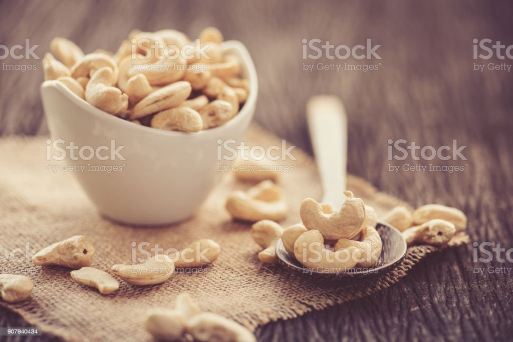 raw cashew nuts in white ceramic bowl on wood table - foto stock