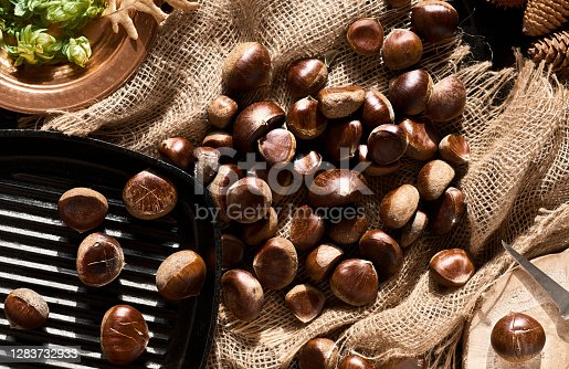Raw chestnuts on burlap on a black background with copy space, preparing for baking in a pan. Top view. Chestnut for christmas or holidays, seasonal dish