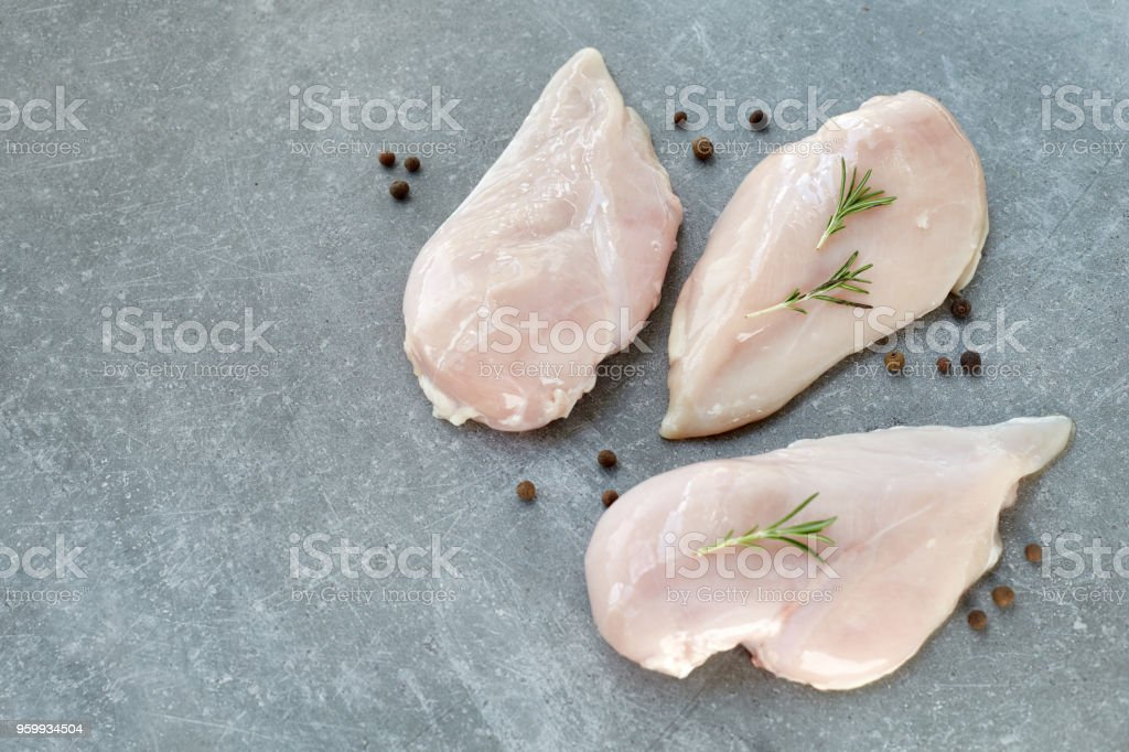 Raw chicken breast fillet with spices and rosemary on a grey stone table. Healthy food. stock photo
