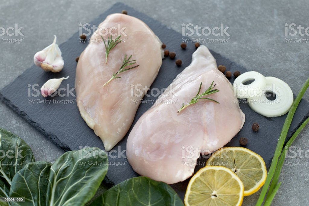 Raw chicken breast fillet with spices and salad leafs on a grey stone table. Healthy food. stock photo