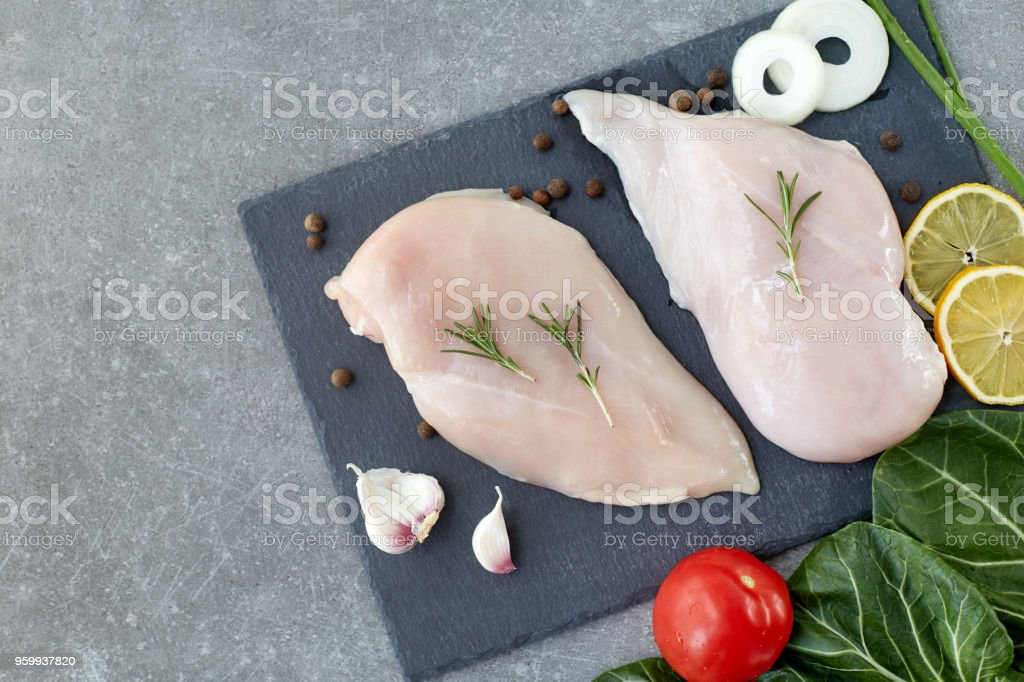 Raw chicken breast fillet with spices and salad leafs on a grey stone table. Top View. Healthy food. stock photo
