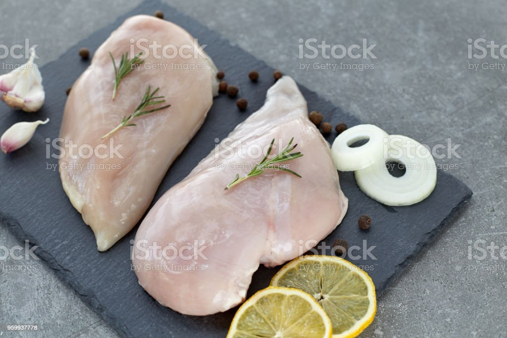 Raw chicken breast fillet with spices, garlic and rosemary on a grey stone table. Healthy food. stock photo