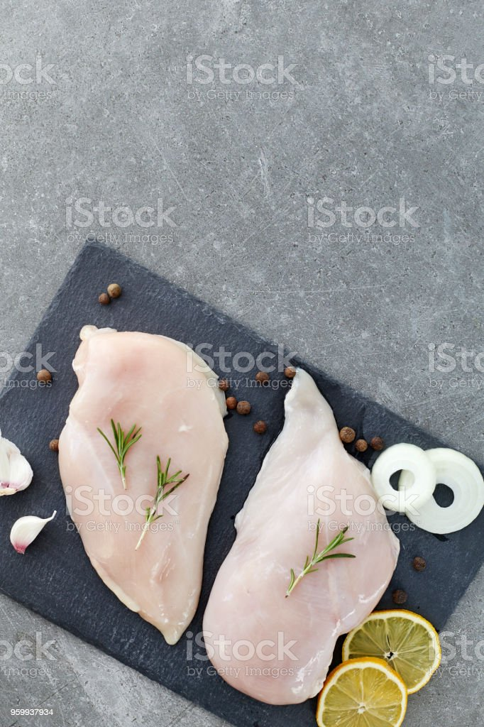 Raw chicken breast fillet with spices, garlic and rosemary on a grey stone table. Top View. Healthy food. stock photo