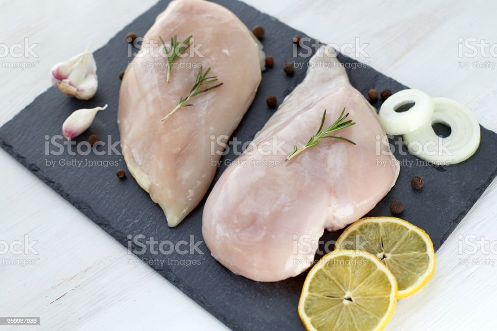 Raw chicken breast fillet with spices, garlic, onion and rosemary on a white wooden table. Healthy food. stock photo