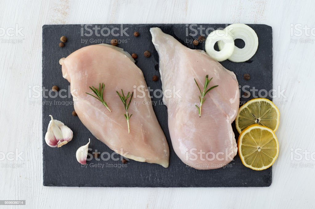 Raw chicken breast fillet with spices, garlic, onion and rosemary on a white wooden table. Top View. Healthy food. stock photo