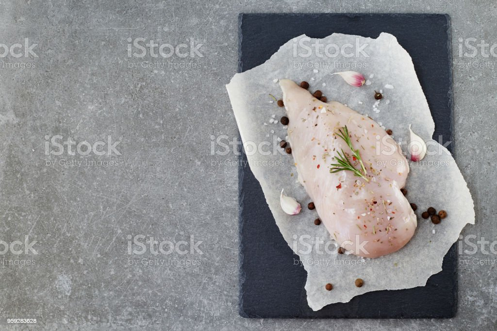 Raw chicken breast with spices, garlic and rosemary on a grey stone table. Top View. stock photo