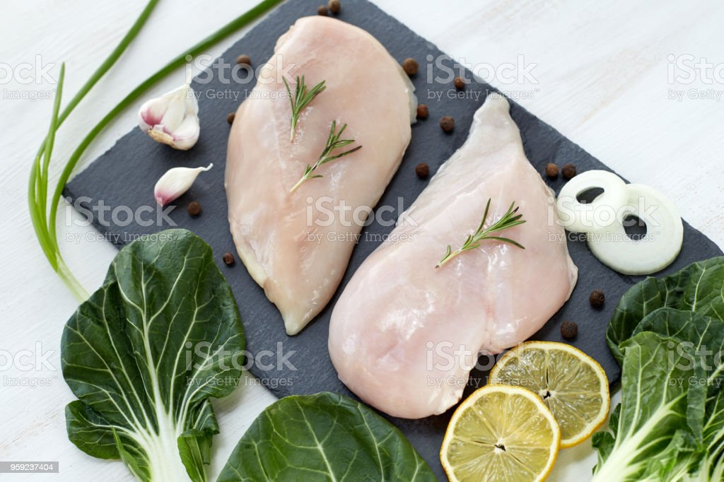 Raw chicken breast with spices, garlic, lemon and green salad leafs on a white wooden  table. Top View. stock photo