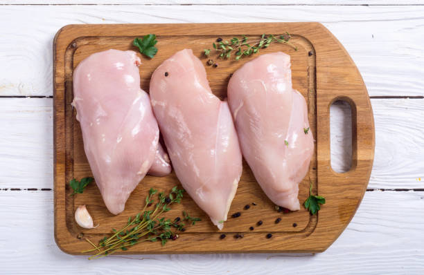 Raw chicken breast with spices Raw chicken breast with spices on cutting board chicken breast stock pictures, royalty-free photos & images