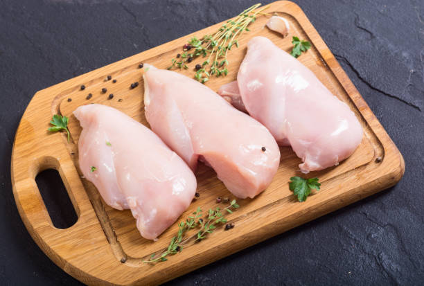 Raw chicken breast with spices Raw chicken breast with spices on cutting board poultry stock pictures, royalty-free photos & images