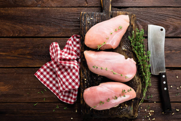 Raw chicken breasts fillets with thyme and spices on wooden cutting board on rustic background, copy space, directly above stock photo