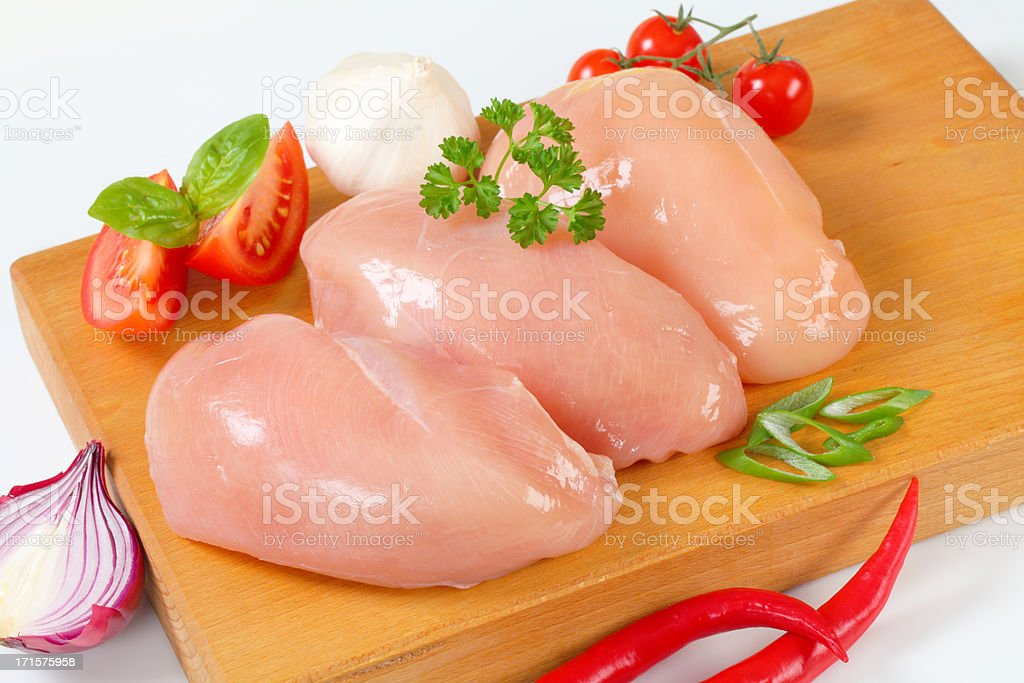 three fillets of raw chicken breasts with vegetables on a wooden...