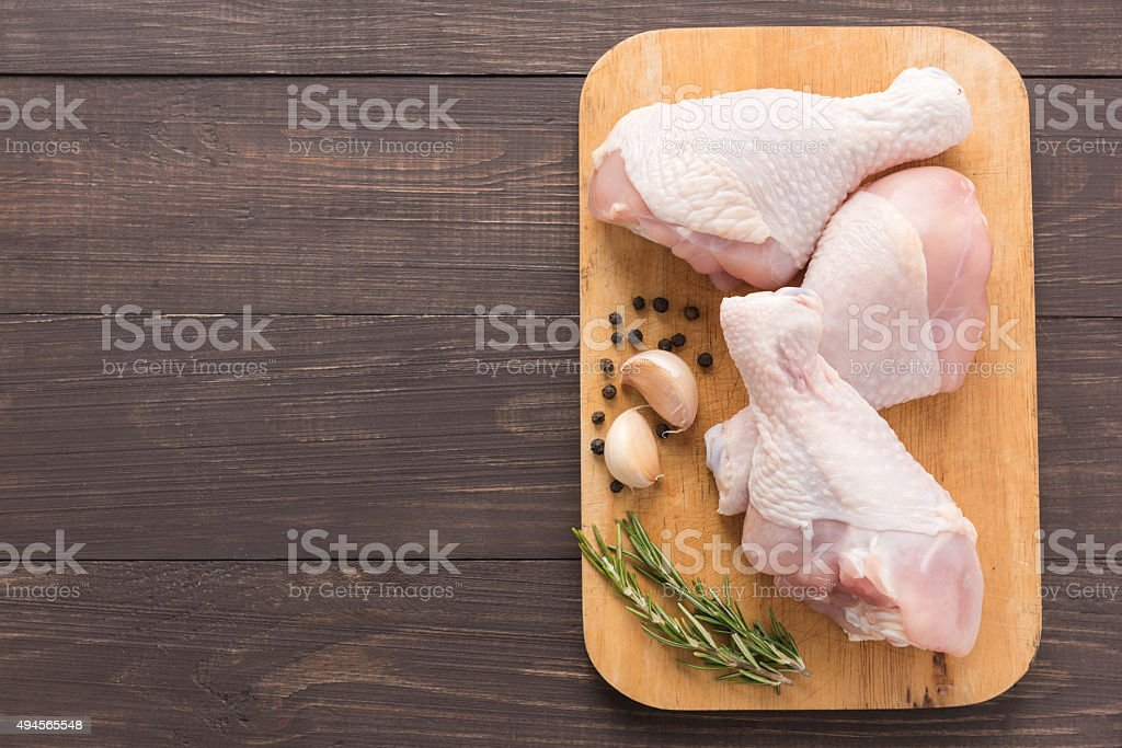 Raw chicken drumsticks on cutting board on wooden background stock photo