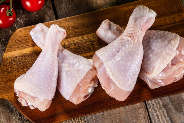 Raw chicken drumsticks on cutting board