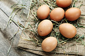 istock raw chicken eggs on burlap on the table. straw is scattered on the table. 1062204482