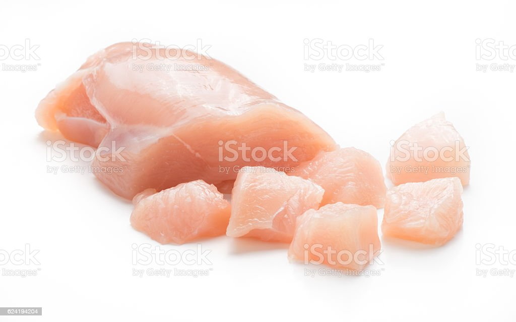 Raw chicken fillet. Small pieces of meat isolated on white. stock photo