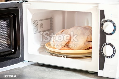 The defrozen raw chicken in the microwave. Selective focus.