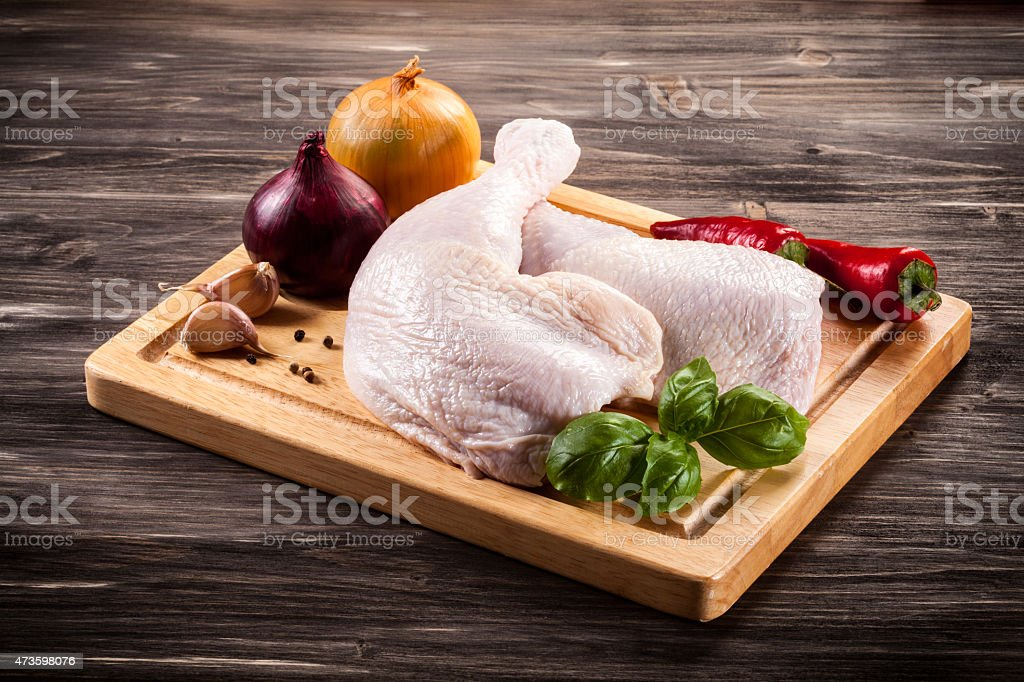 Raw chicken legs on a wooden board with onions and a chilli stock photo