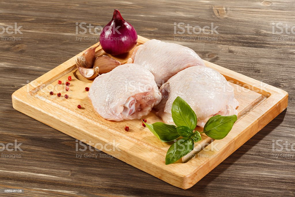 Raw chicken legs on cutting board stock photo