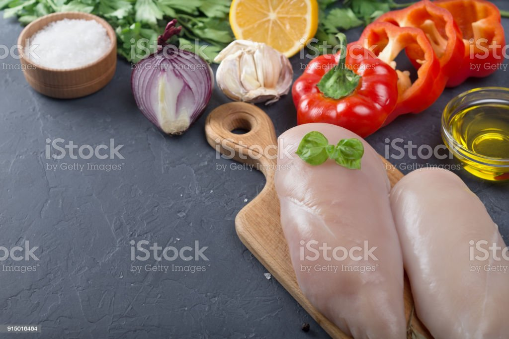 raw chicken meat with onion and pepper stock photo