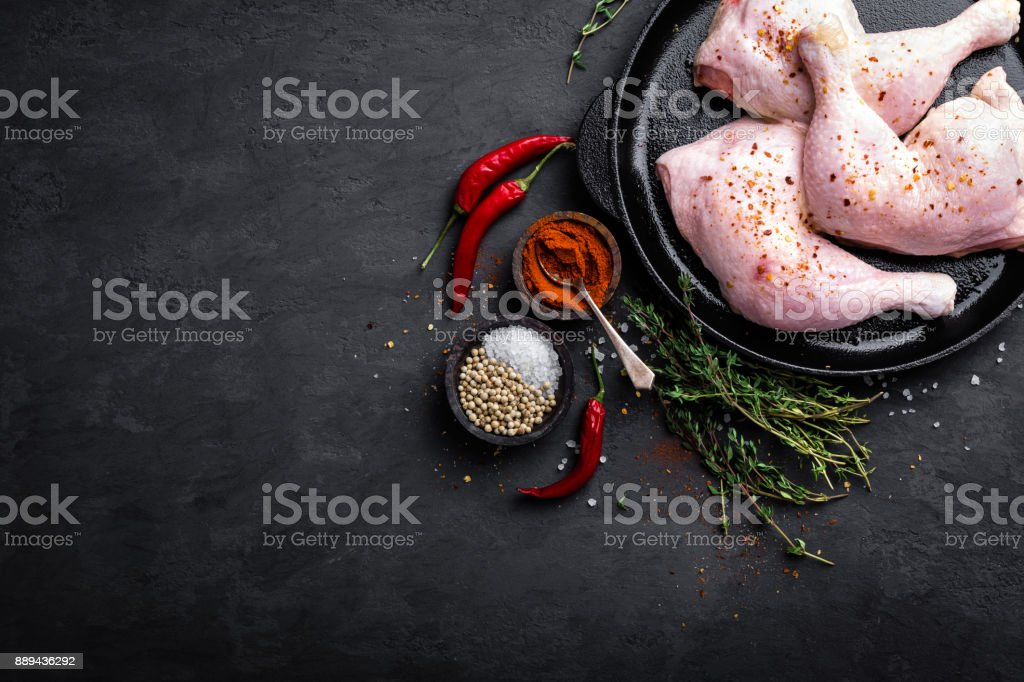 Raw chicken quarters, legs in a pan on a dark background. Top view. stock photo