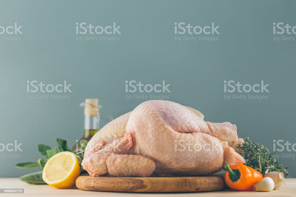 Raw chicken with ingredients for cooking and vegetables on kitchen table behind blue background. Horizontal royalty-free stock photo