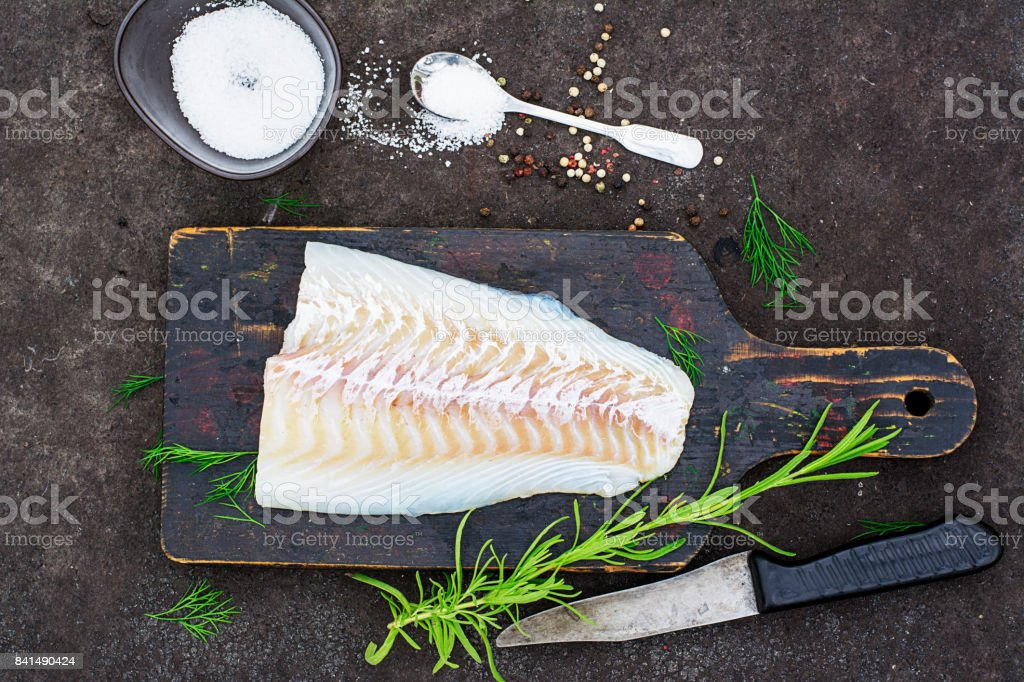 Raw cod before cooking on a black chopping Board with herbs and sea salt on a dark background. Top view stock photo